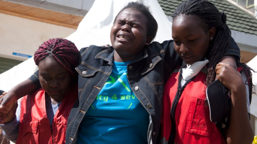 Kenya Red Cross staff help a woman after she viewed the body of a relative killed in last Thursday's attack on Garissa University College in northeastern Kenya, at Chiromo funeral home, Nairobi, Kenya. Al-Shabab gunmen rampaged through the university at dawn Thursday, killing over 140 people in the group's deadliest attack in the East African country.